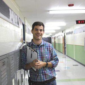 Principal Bryan Gibson leans against a locker in a school hallway