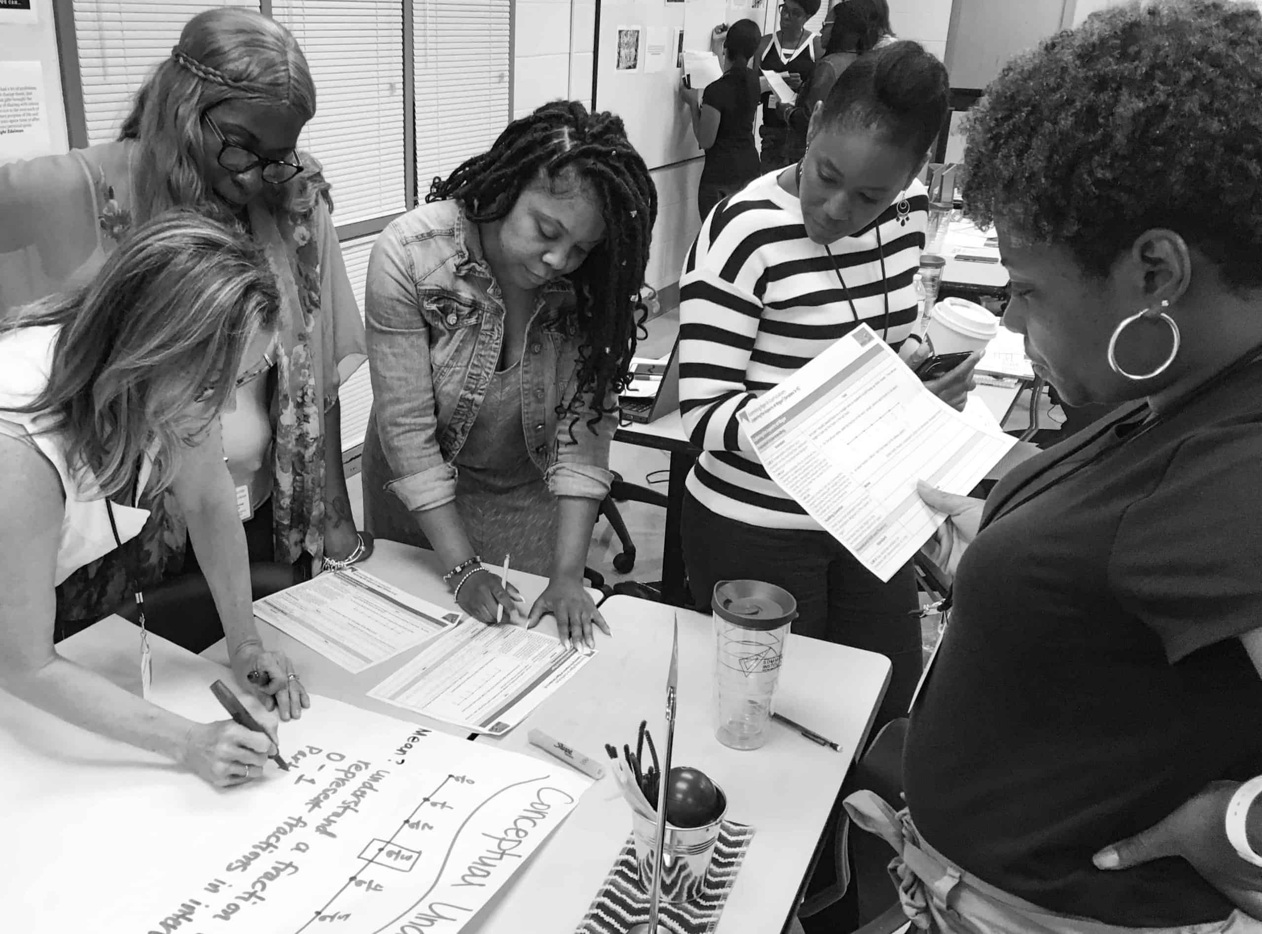 Five leaders work on a math problem during a PLC in Atlanta
