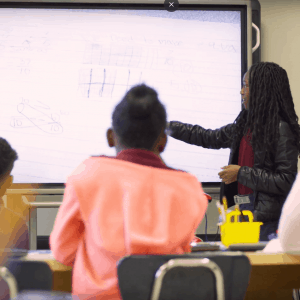 A teacher models a lesson to her class using a smart board