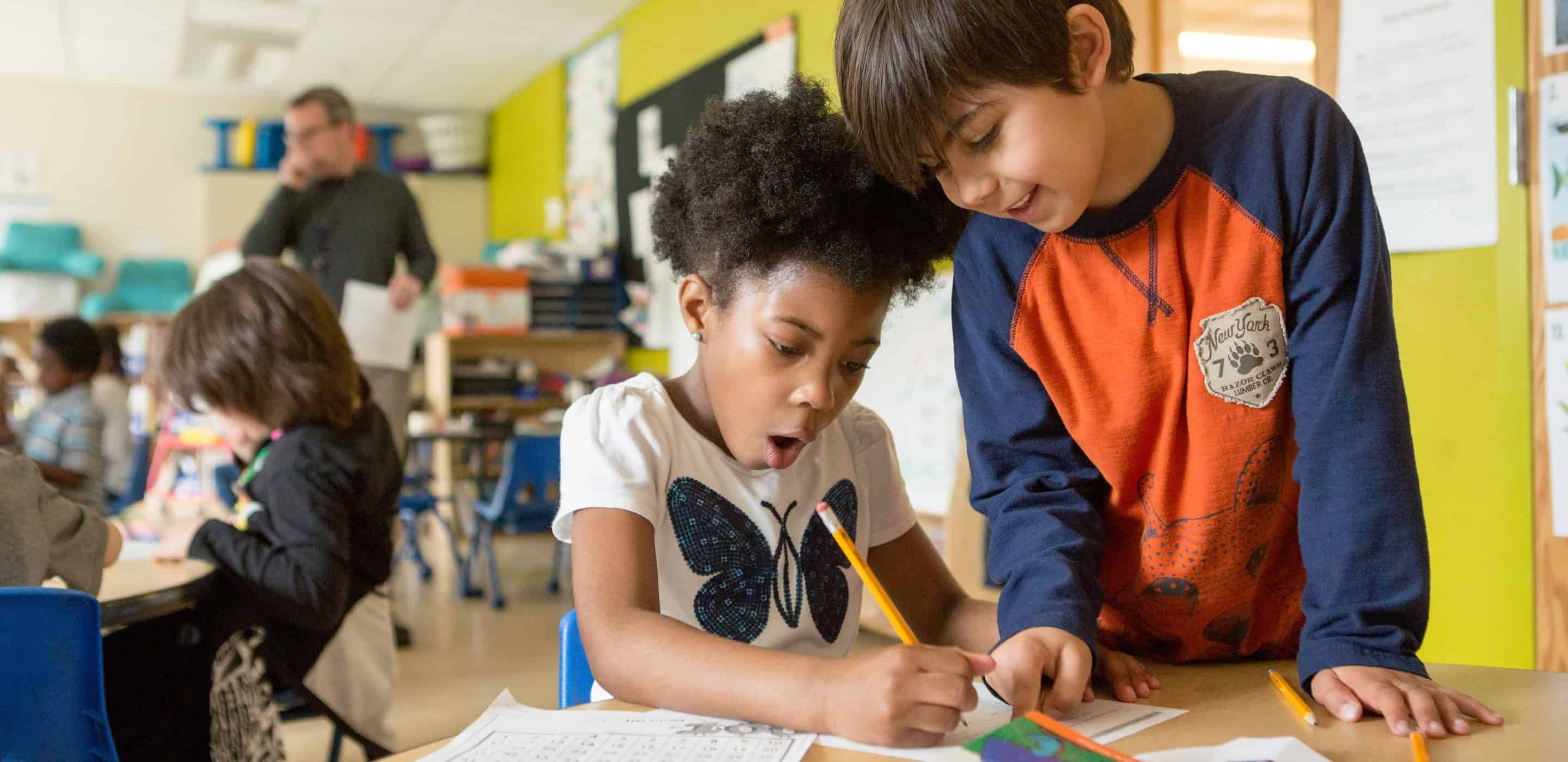A boy and girl work together on an assignment