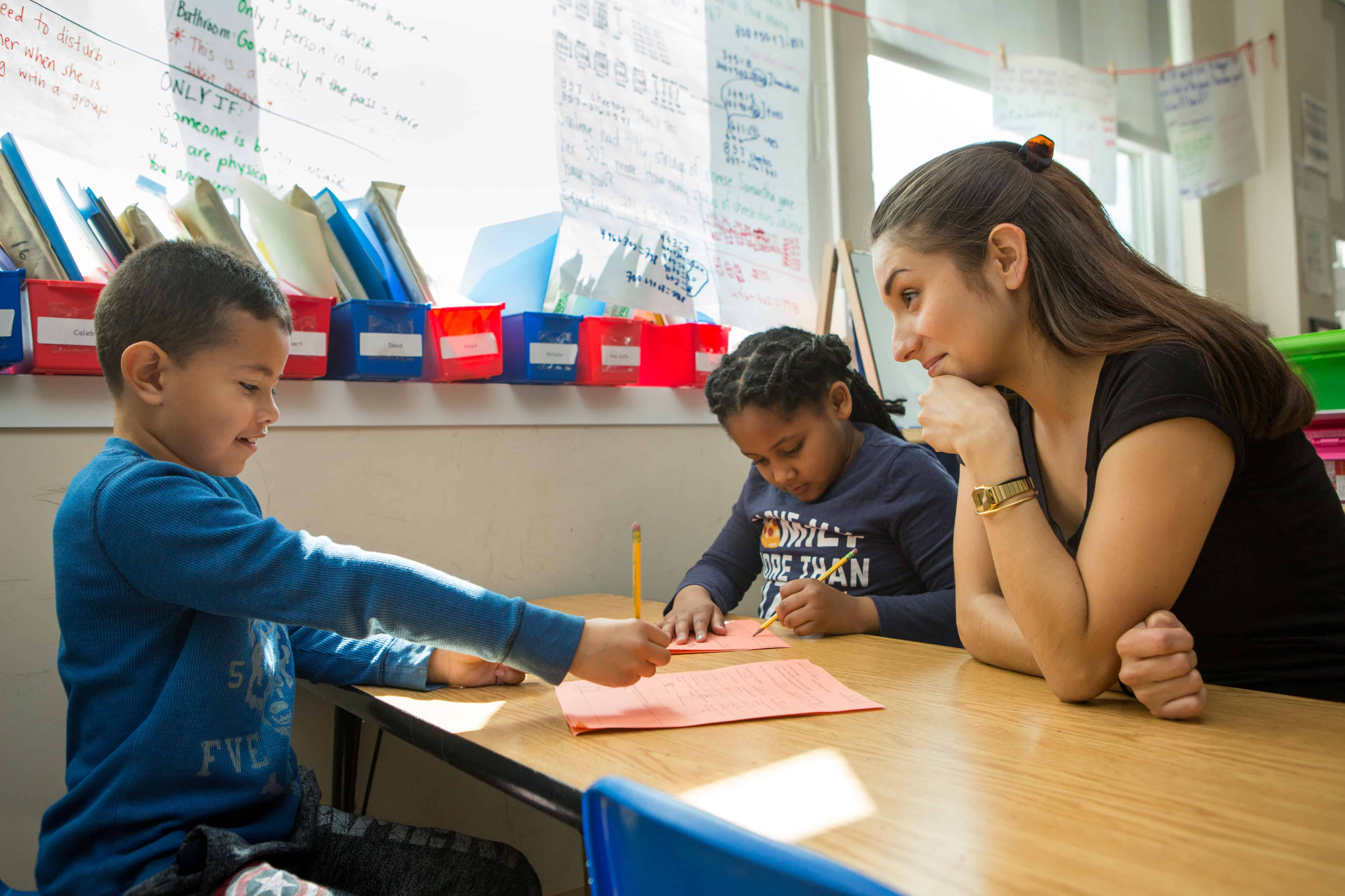 A teacher at Capital City PCS looks on as two students write