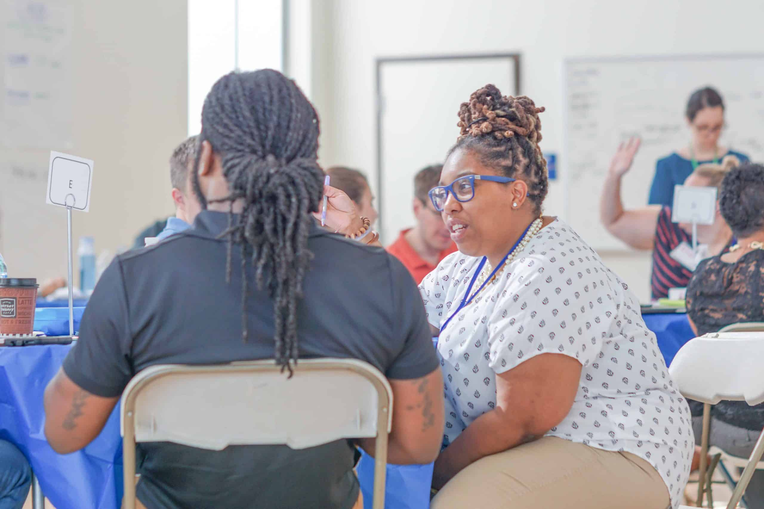 Two DC educators talk to each other during a session