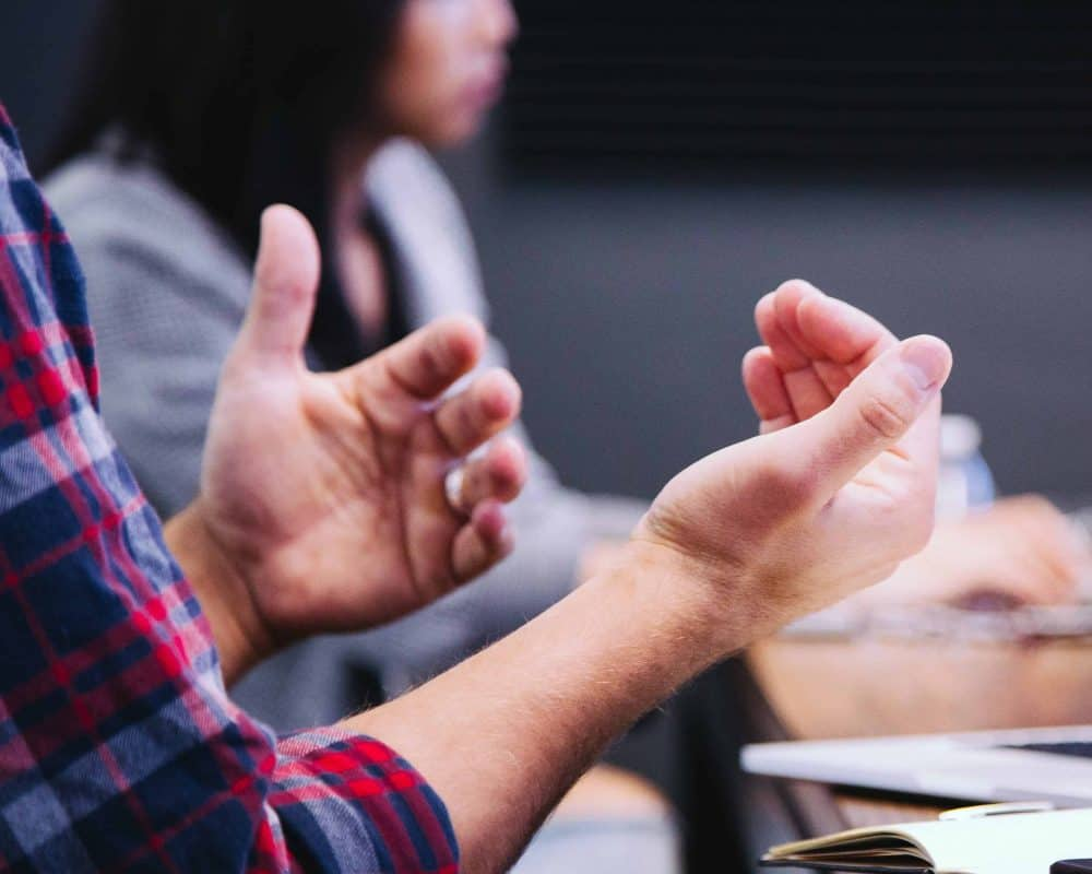 Two hands are gesturing as if in the middle of speech