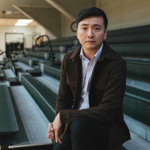 Chong-Hao Fu sits on bleachers in empty school gym