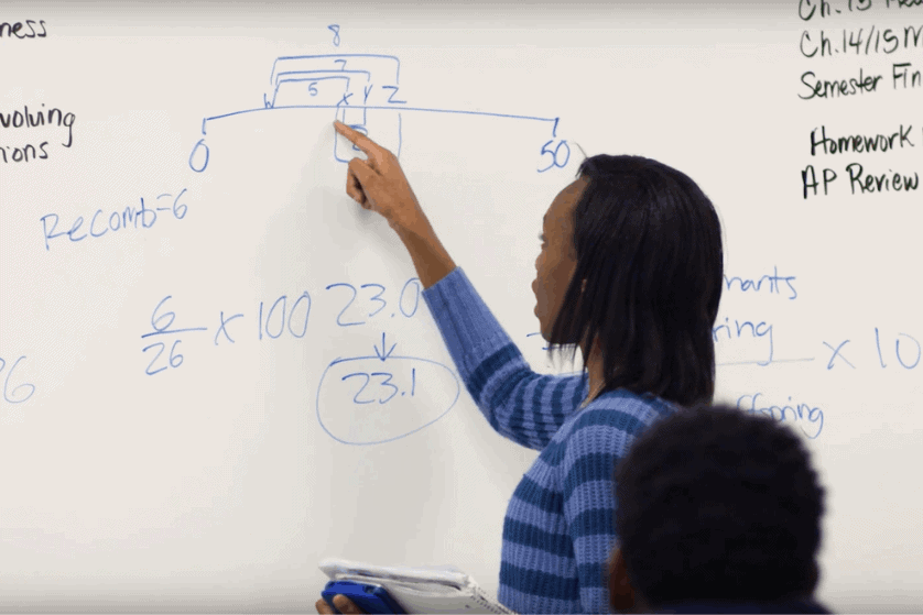 A girl explains her solution to a math problem in front of a white board