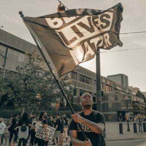 A man waves a Black Lives Matter flag at a protest