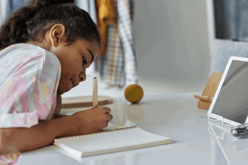 girl in a tie dye shirt writing in a notebook