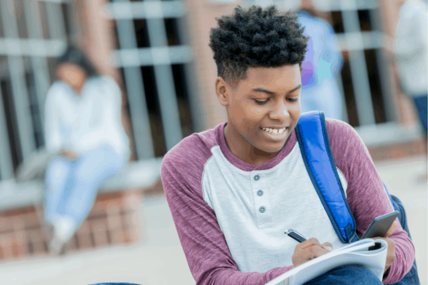Black middle school student writing in his notebook outside