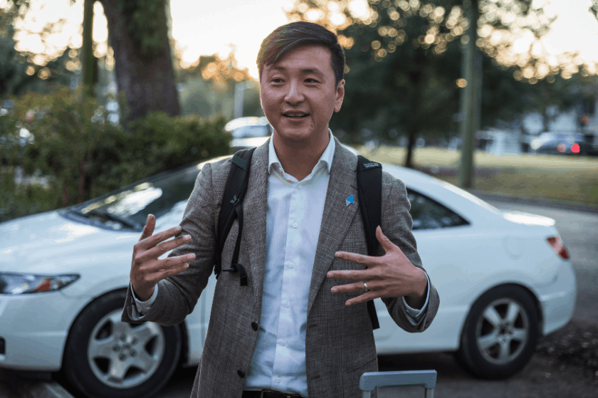 Chong-Hao Fu talking in front of a car while wearing a backpack
