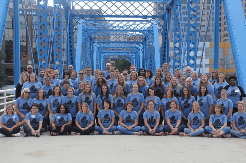 a group of about 30 grand rapids leaders pose in rows wearing matching light blue tshirts on a blue bridge
