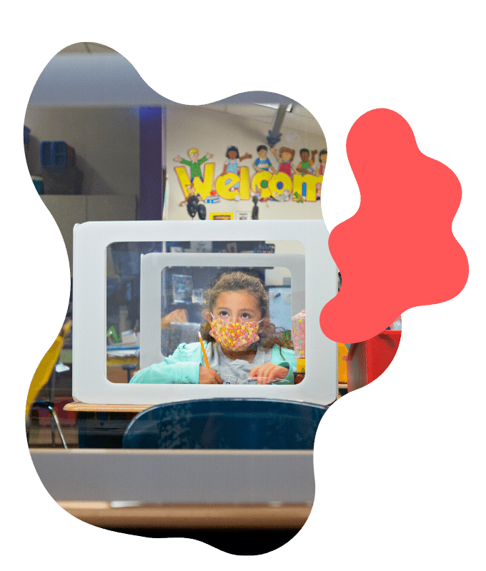 girl sits at a desk behind a barrier