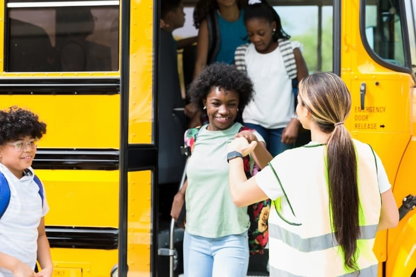 a group of students walk off a school bus